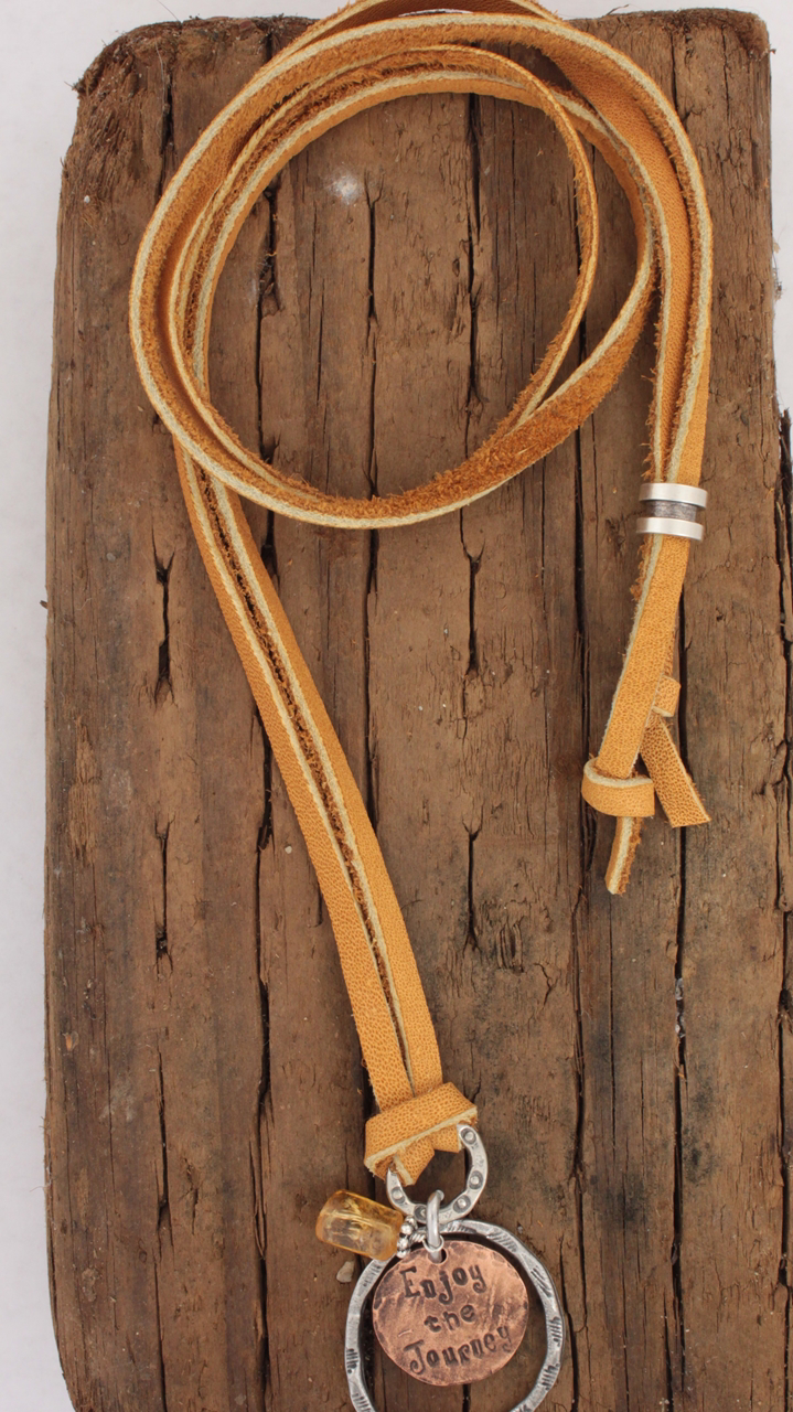 enjoy the journey leather necklace on wood