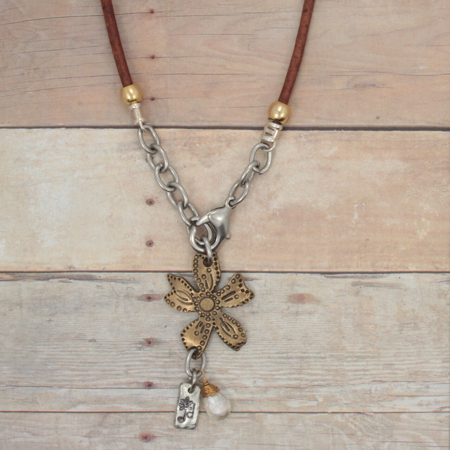 brown leather wildflower necklace on wood