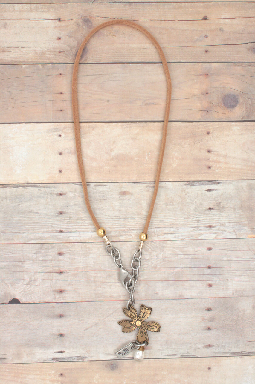tan leather wildflower necklace on wood
