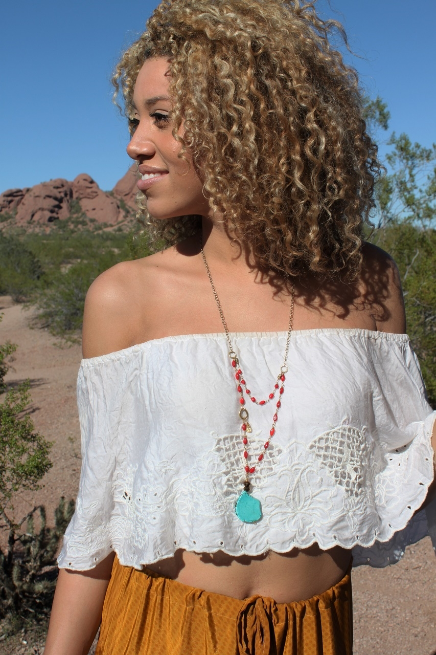 Layered-coral-necklace-with-truquoise-pendant-on-black-model-outdoors