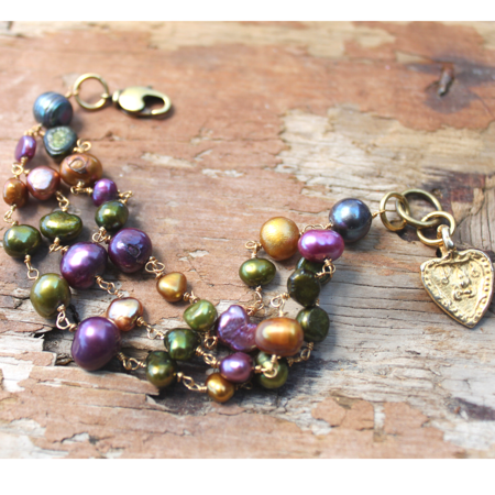 Colorful pearl cluster gold heart bracelet on wood