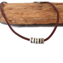 brown-leather-silver-cylinder-necklace-against-wood-white-background