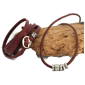 brown-leather-hammered-silver-buckle-wrap-bracelet-brown-leather-silver-cylinder-necklace-against-wood-white-background
