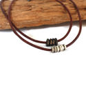 two-brown-leather-silver-cylinder-black-hex-nut-necklaces-against-wood-white-background