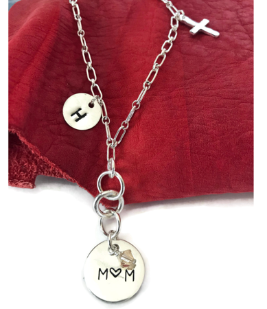 Sterling-silver-chain-mom-charm-necklace-on-red-leather-background