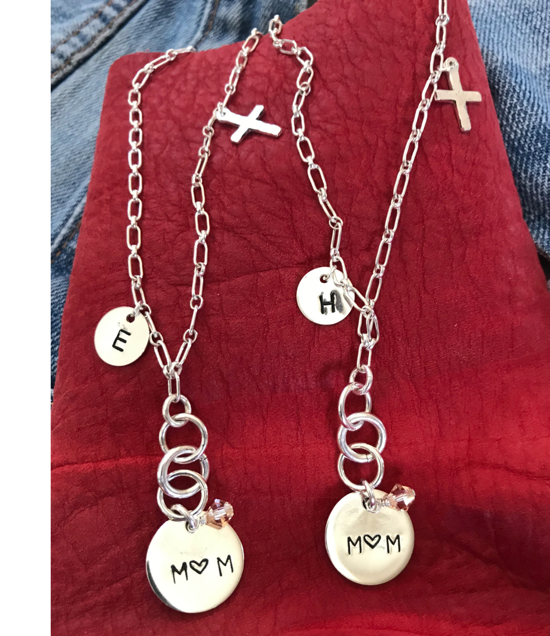 two-Sterling-silver-chain-mom-charm-necklaces-on-red-leather-and-denim-background