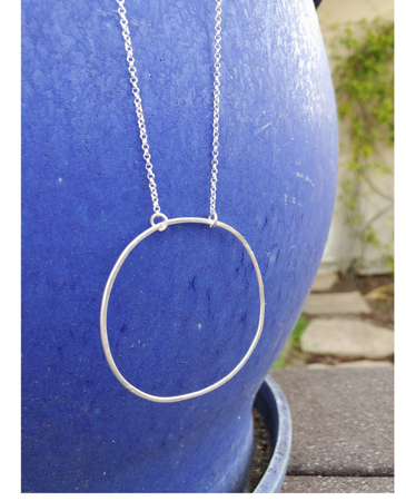 silver circle necklace on blue pot