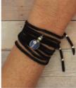 black suede bracelet wrap on wrist on wood