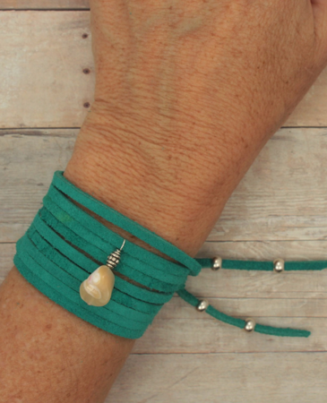 Teal suede wrap bracelet on wrist on wood