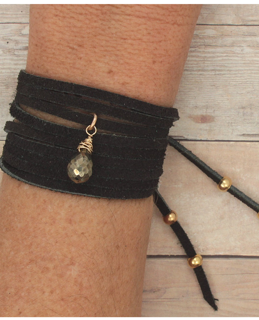 black suede pyrite wrap bracelet on wrist on wood