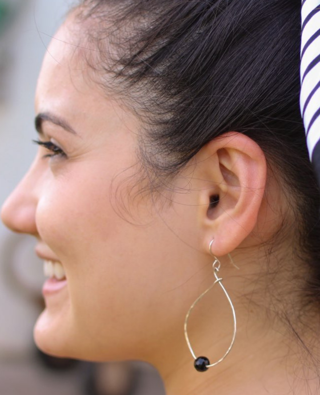 Sterling onyx hoop earrings on female profile