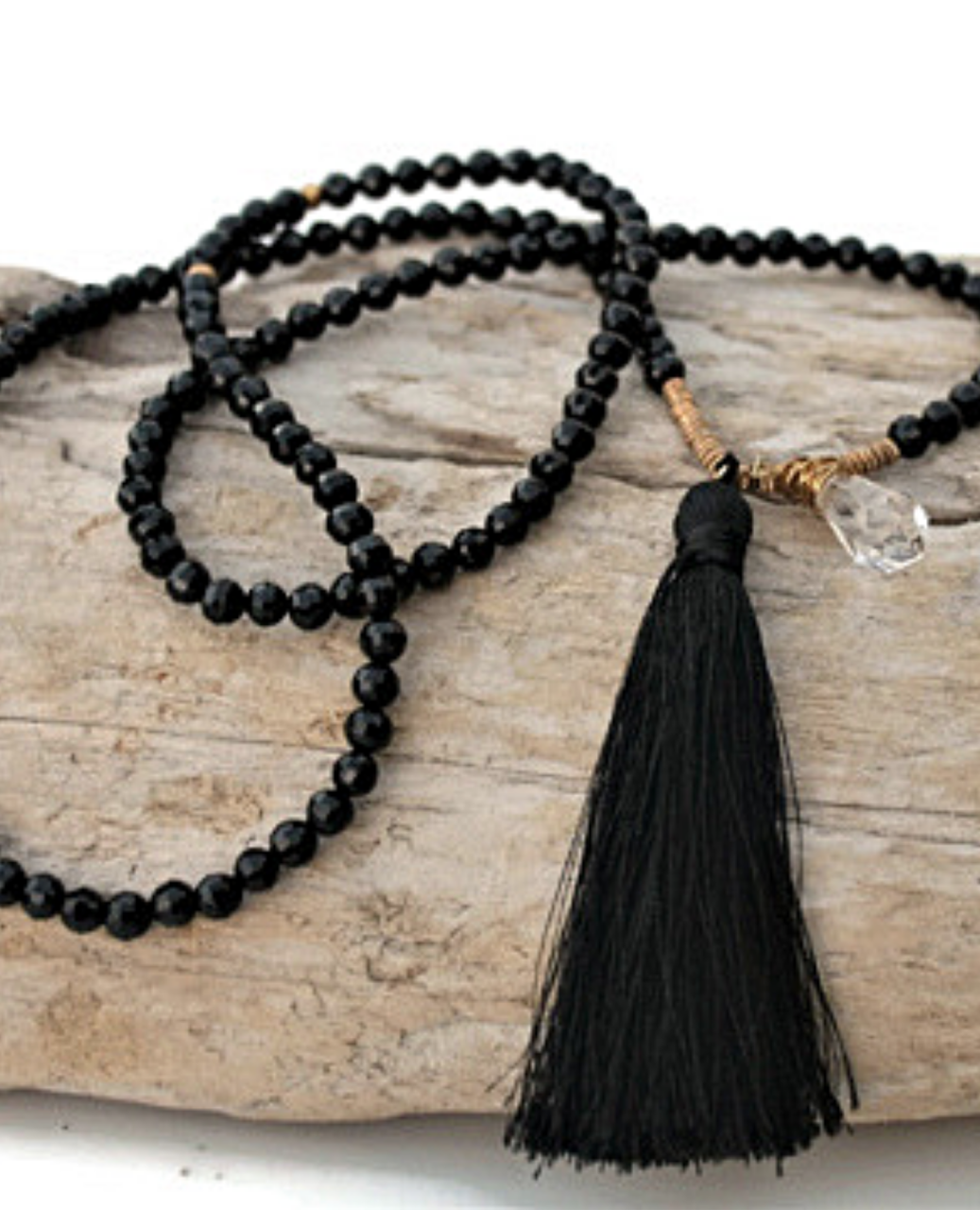 Long black beaded tassel necklace on wood