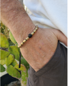 brass and black beaded men's bracelet with hand in pocket