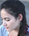 silver textured hoop earring on dark haired model