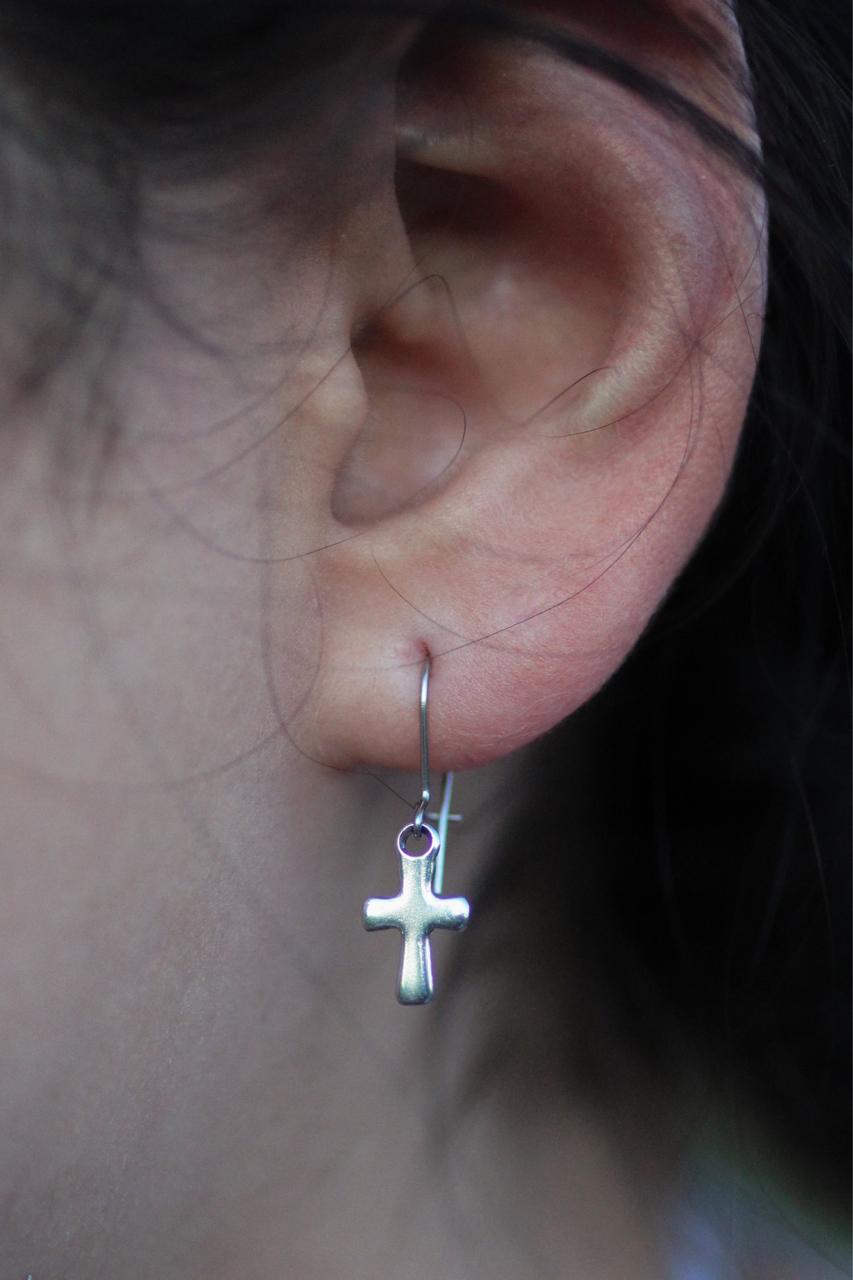 silver cross earring on ear