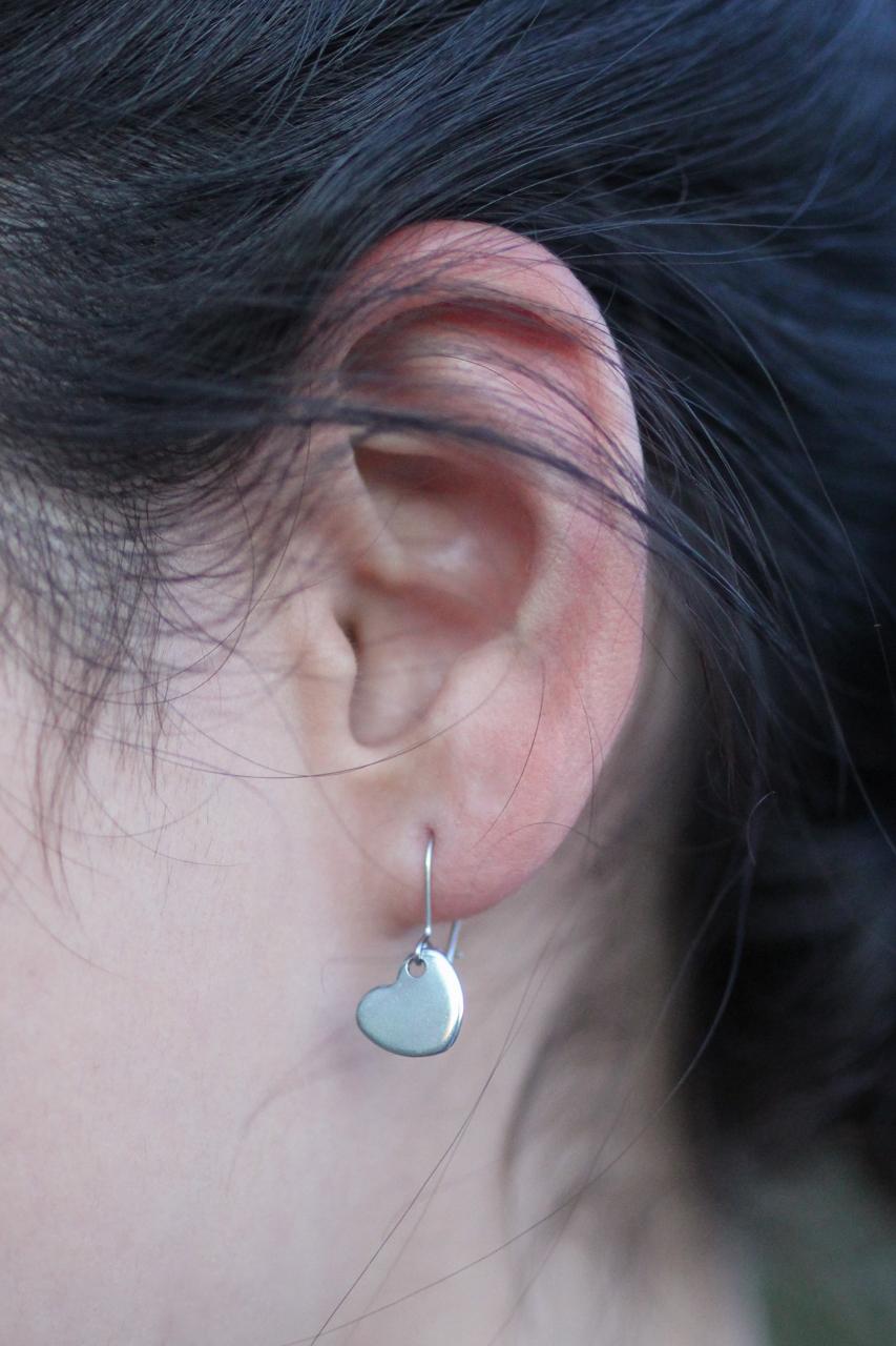 small silver heart earrings on ear