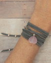 gray suede wrap bracelet with pink stone on arm