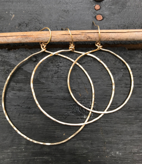 various sized gold  hoop earrings on black background