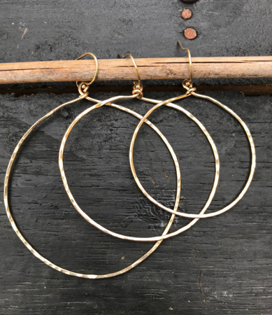 various sized gold  hoop earrings on black background