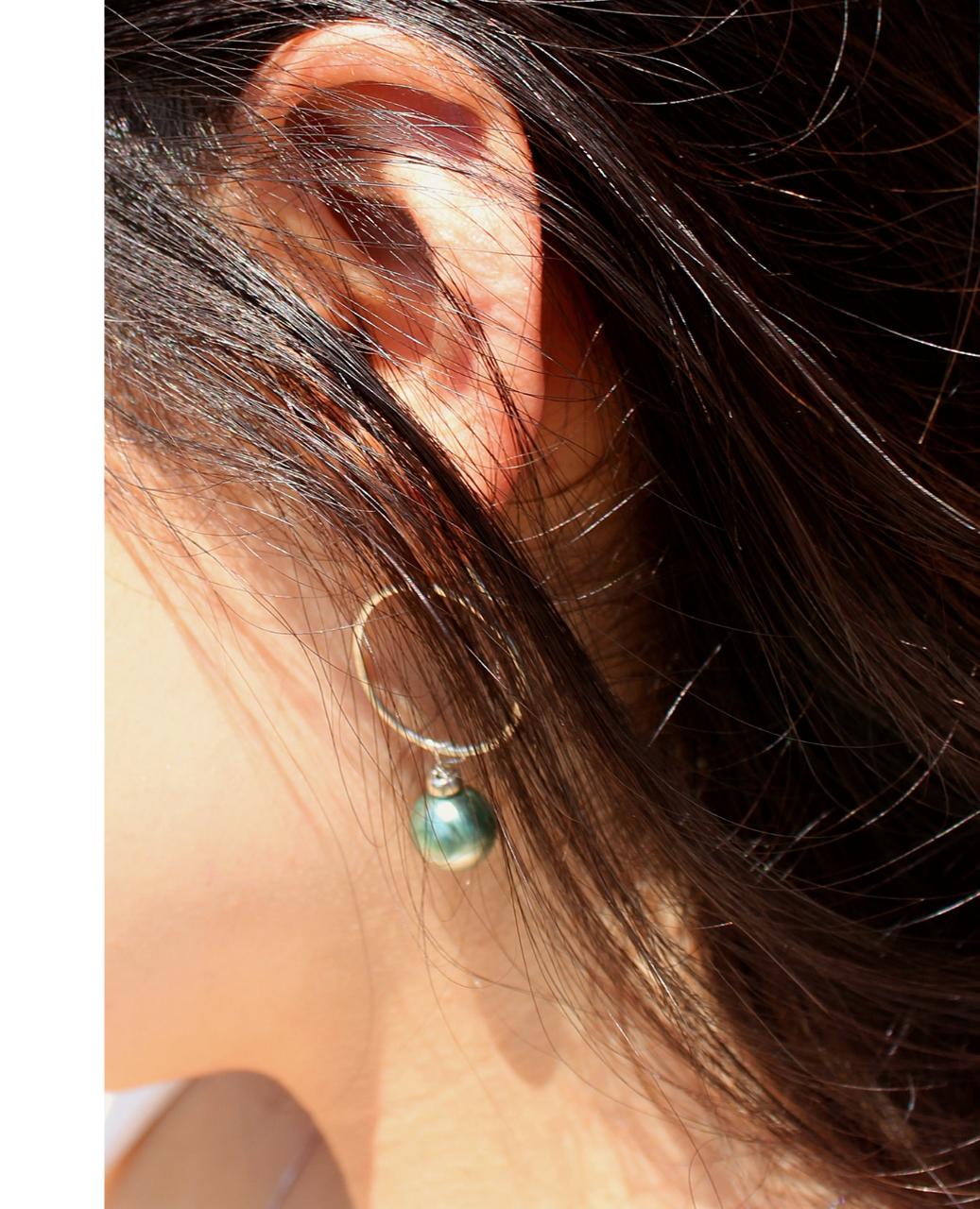sterling hoop green pearl earring on earlobe and hanging hair