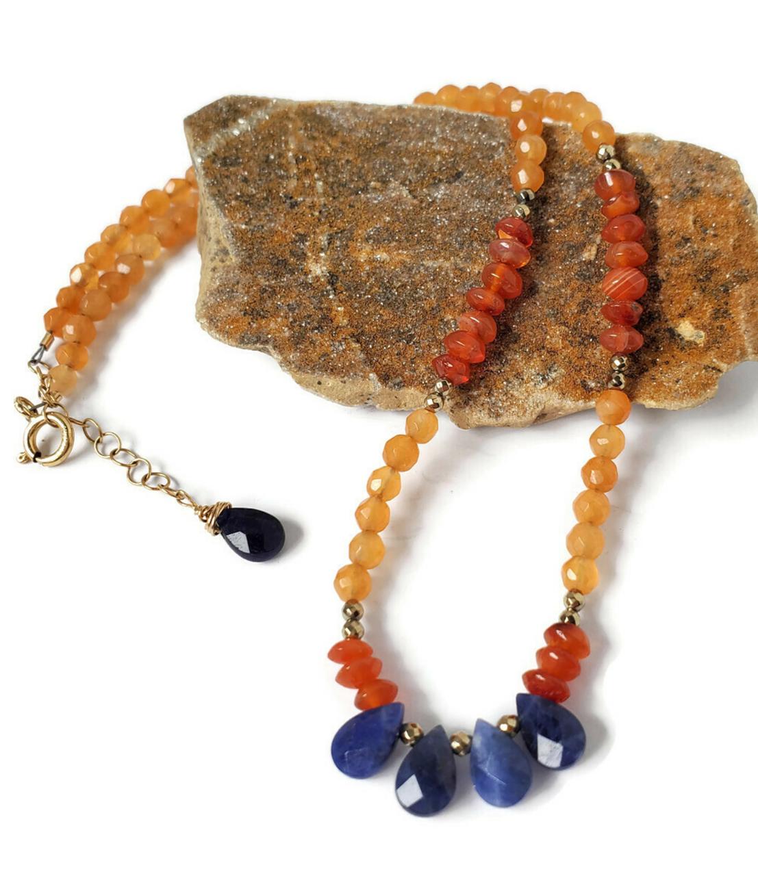 orange  & blue gemstone collar necklace on rock