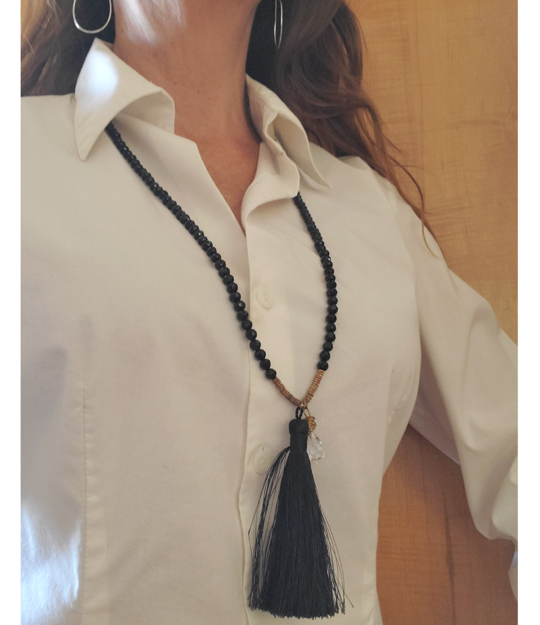 long black tassel necklace worn with white blouse