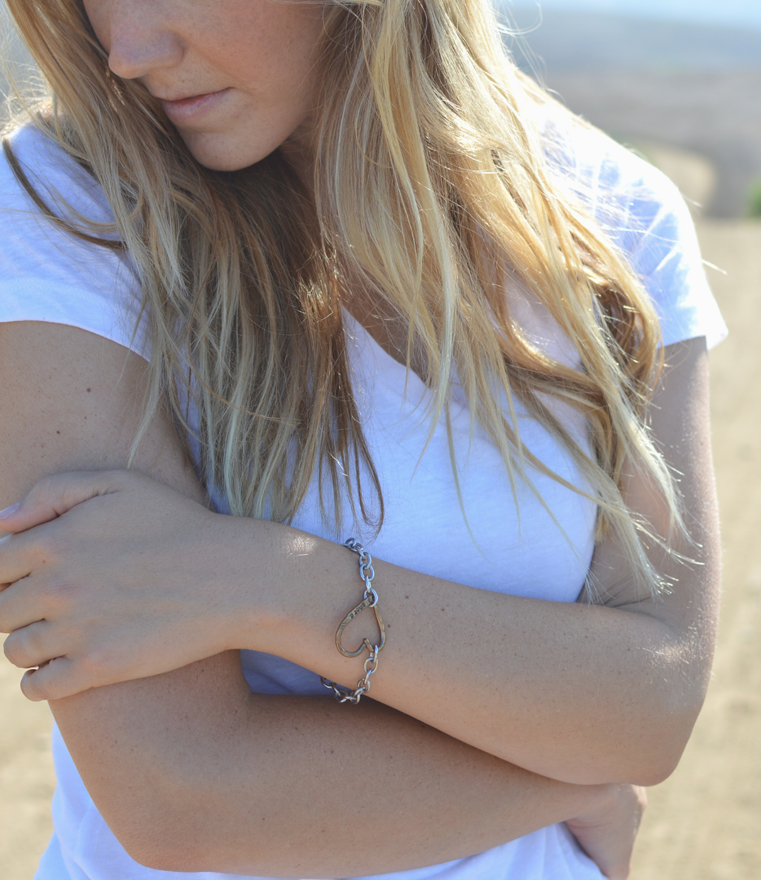 heart bracelet on crossed arms