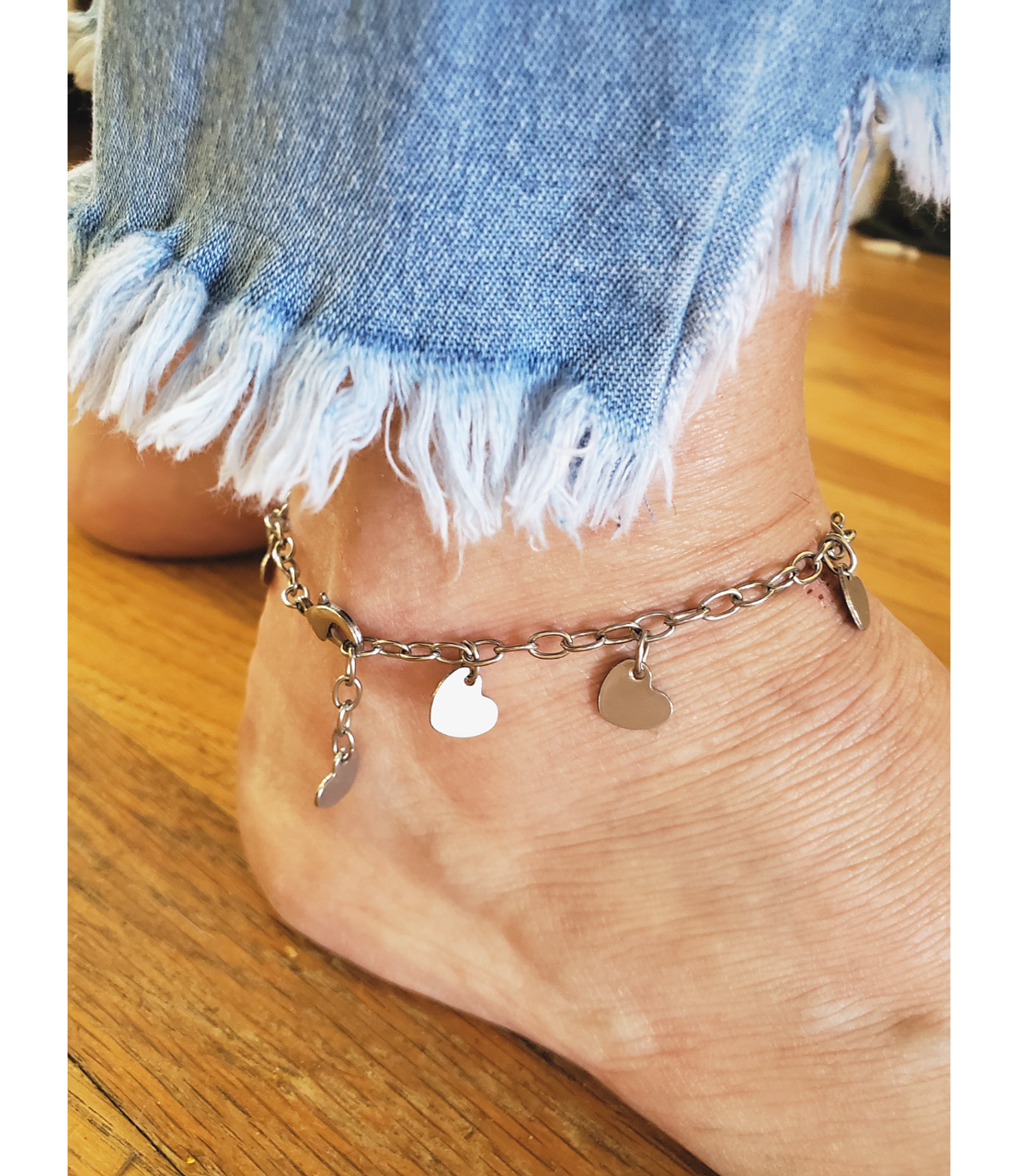 blue jeans and silver heart anklet on foot