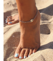 barefoot in the sand with a silver chain tag anklet