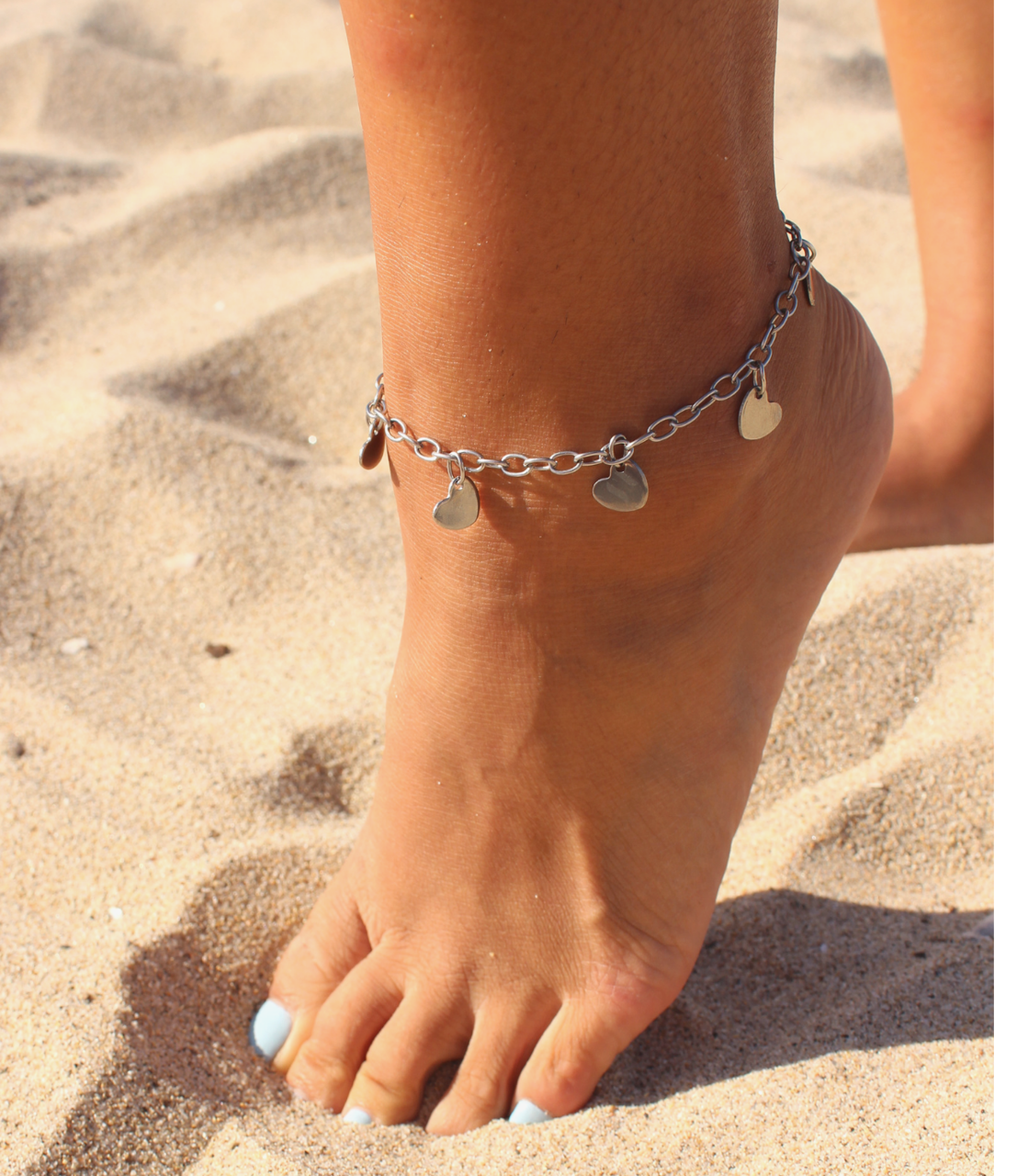 barefoot on the sand with a silver multi heart anklet