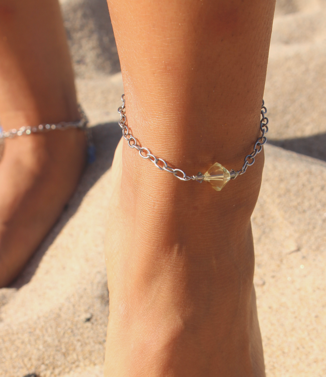 yellow stone chain anklet on foot at beach