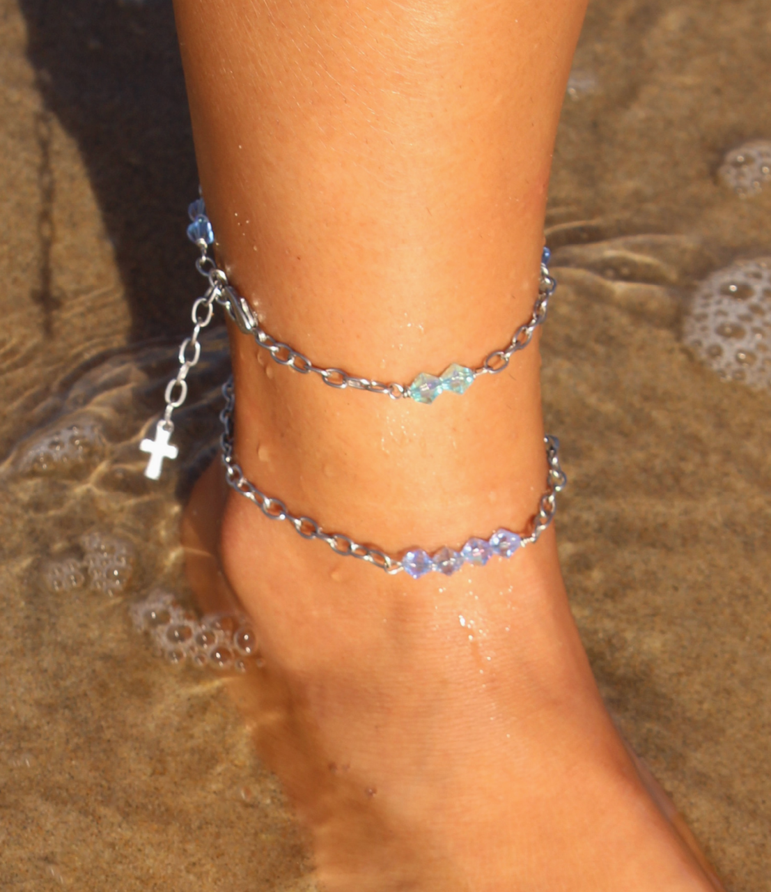 two layered anklets on foot in sand and water