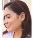 Big gold hoop earrings on model with long dark hair