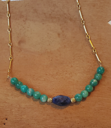 blue and green gemstone necklace on wood
