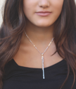 gold & silver stick necklace on dark haired models neck