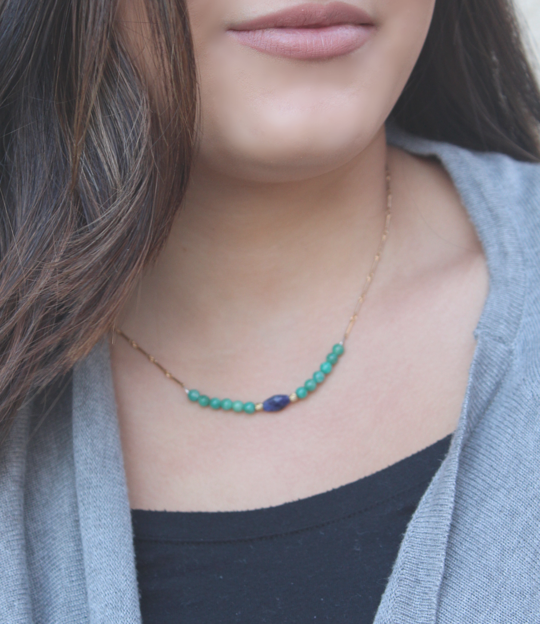 blue & green gemstone gold chain necklace on dark haired model