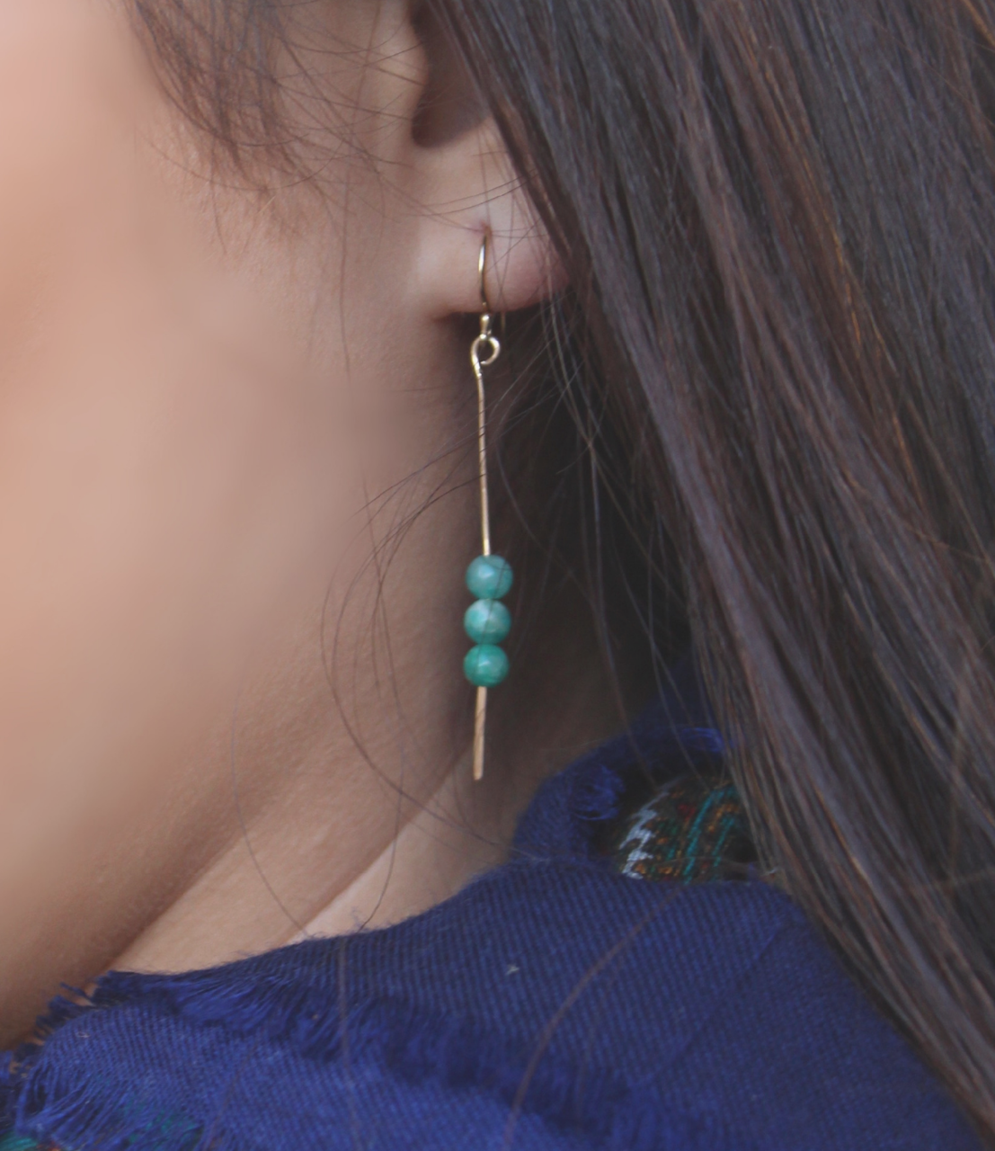 gold stick gemstone earrings on model ear with neck scarf