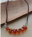 Brown leather orange gemstone necklace on wood