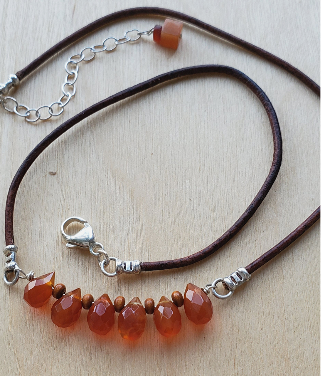 Casual Brown leather orange gemstone necklace on wood