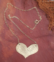 Gold heart delicate chain necklace on texture material