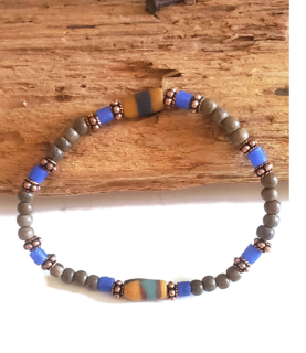 a mix of neutrals & bold color beaded bracelet on wood