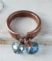 top view of hammered copper cuff ring with blue crystals on white distressed wood
