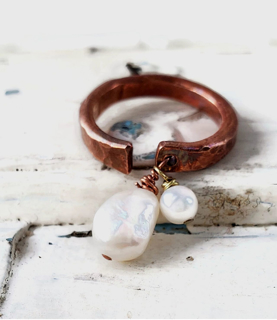 White freshwater pearl copper cuff ring on white distressed wood