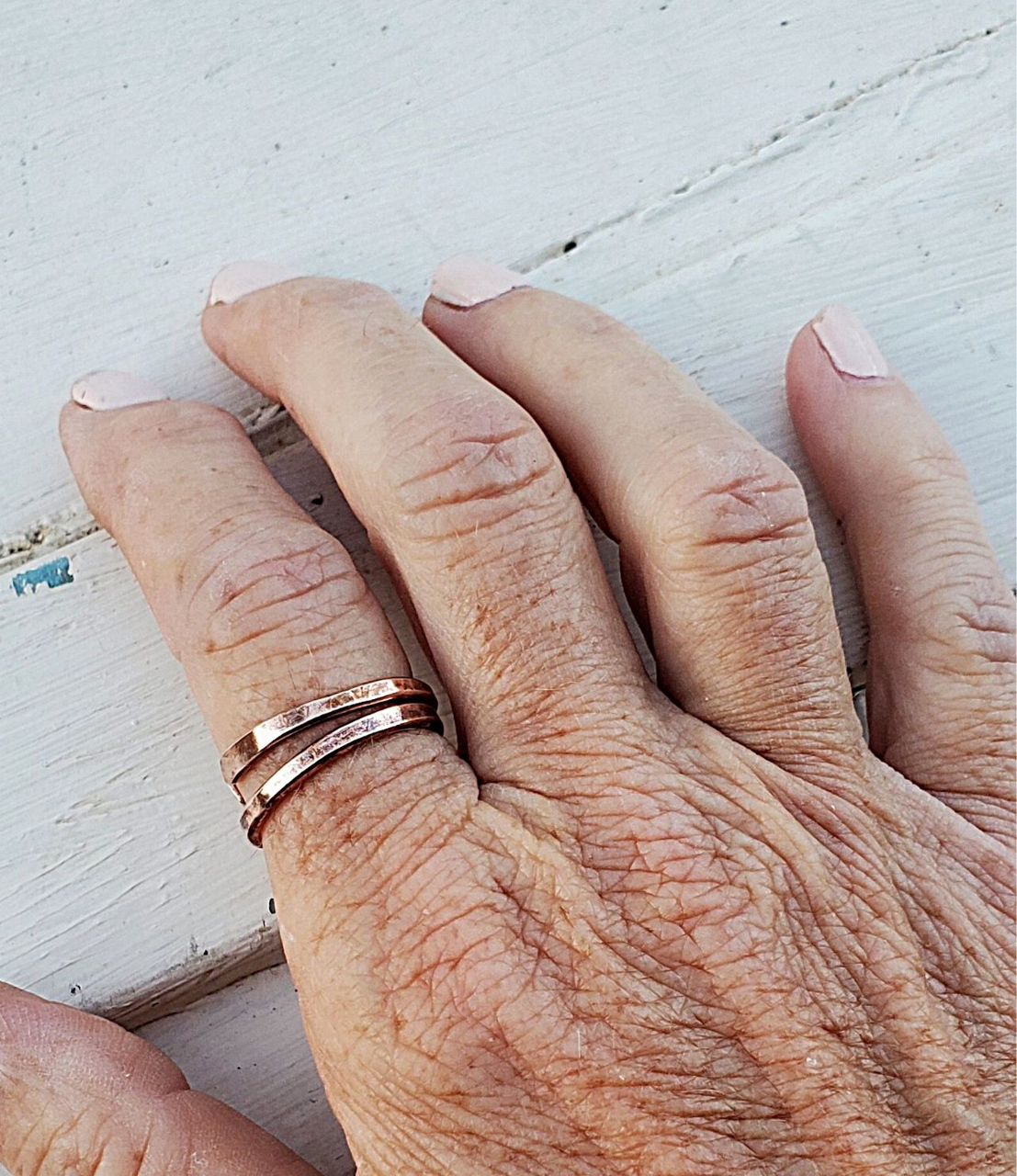 two bronze cuff rings worn on pointer finger