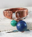 Antimicrobial copper cuff ring with blue gemstone on white distressed background
