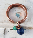 Handcrafted artisan copper cuff ring with blue gemstone on white distressed background