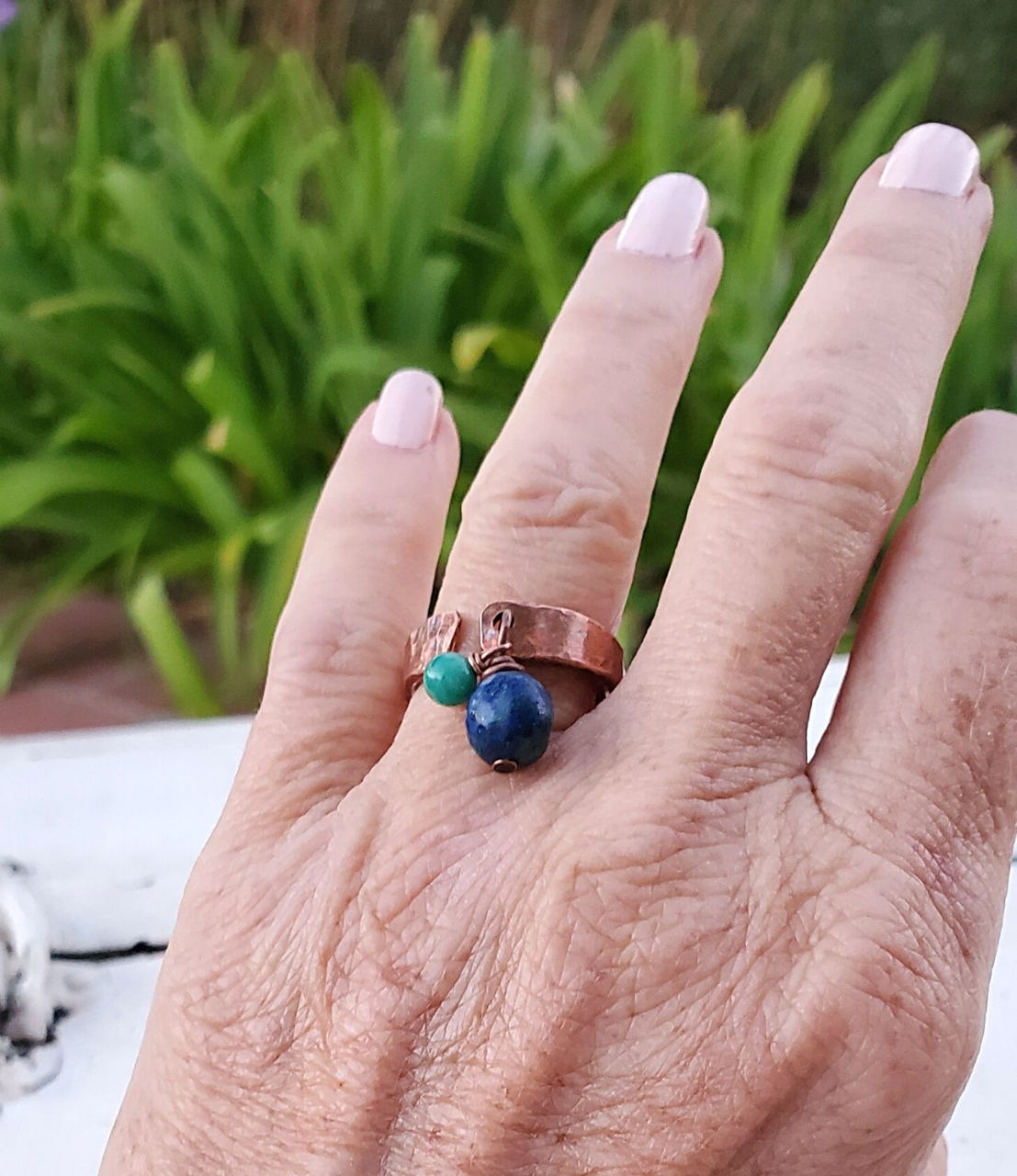 Wearing an artisan copper cuff ring with blue gemstone on white distressed background