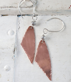 Handcrafted copper & silver earrings on white distressed wood