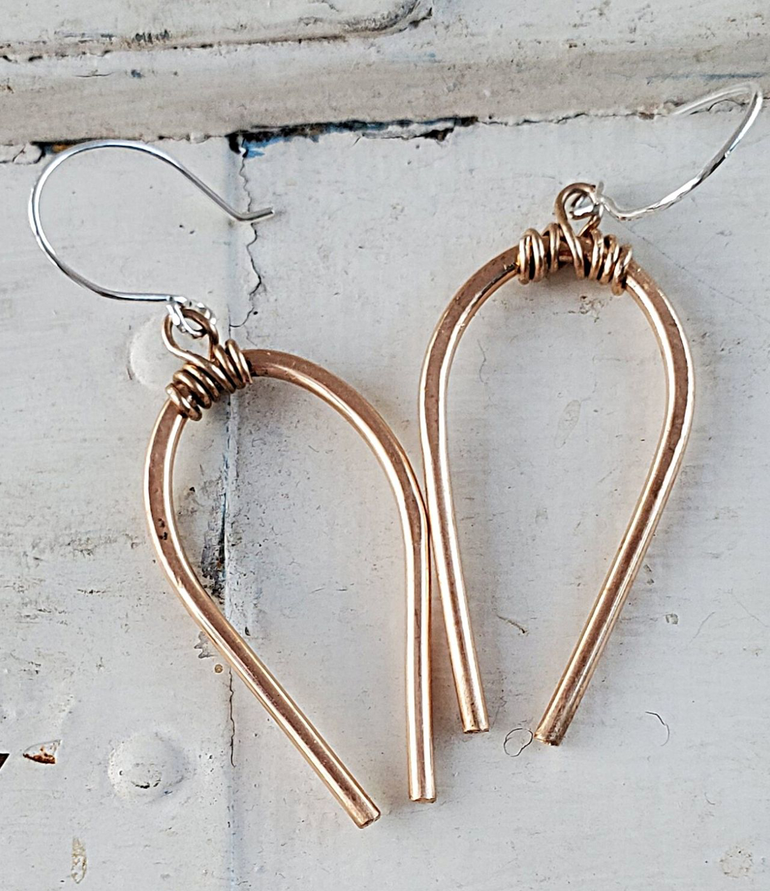 Casual Bronze Horseshoe earrings on white distressed trunk