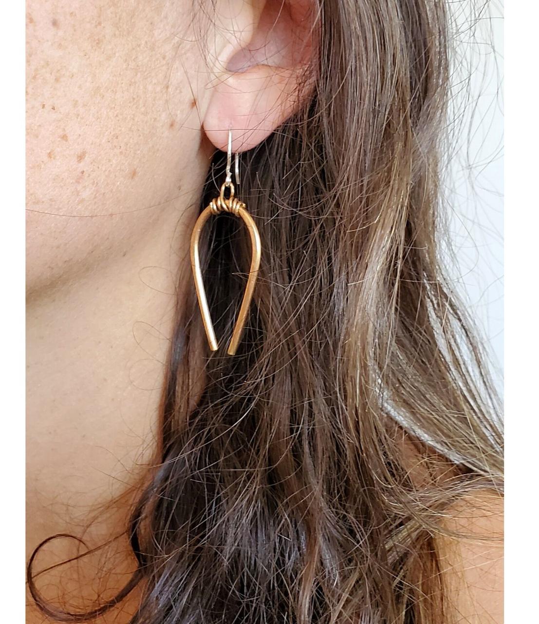 wearing  Casual Bronze Horseshoe earrings on white distressed trunk